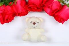 Vit nallebjörn som omges av rosa rosor på en vit trätabell Mall för mars 8, mors dag, valentin dag Arkivfoton