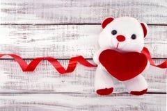 Vit nallebjörn som rymmer en röd hjärta på vit lantlig träbaksida Fotografering för Bildbyråer