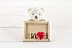 Vit nallebjörn som rymmer plattan med hjärtor Begrepp på 14 Februari Arkivbild