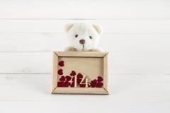Vit nallebjörn som rymmer plattan med hjärtor Begrepp på 14 Februari Arkivfoton