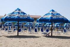 Vit och blått satte fransar på strandparaplyer Arkivfoton