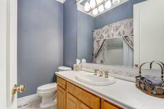 Vit- och blåttbadrum i ett lyxigt landshus royaltyfri foto