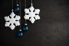 Vit- och blåttxmas-prydnader på svart träbakgrund Glad julkort Arkivbilder