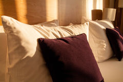 Vit och bordoen kudde på lyxig säng i rum Arkivbilder