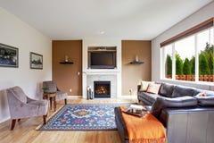 Vit och brunt tonar vardagsrum med spisen och tv Arkivbilder