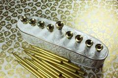 Vit och guld- keramiska Chanukkahmenoror med metalliska guldstearinljus beside på en bakgrund av metalliska bladguld Royaltyfria Bilder