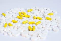 Vit- och gulingpreventivpillerar på en vit bakgrund arkivfoton
