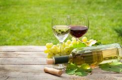 Vit och rött vinexponeringsglas och flaska med gruppen av druvor Royaltyfria Bilder