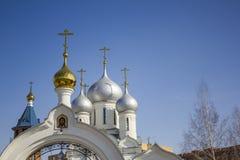 Vit ortodox kyrka med att blänka kupoler och en symbol på en bakgrund av ren blå himmel fotografering för bildbyråer