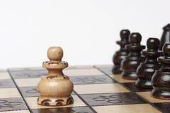 Vit pantsätter den utmanande armén av svarta schackstycken Royaltyfri Bild