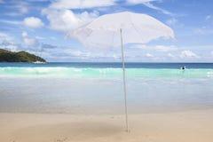 vit parasoll på stranden arkivbilder
