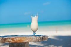 Vit pinacolada på strandtabellen Arkivfoton
