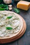 Vit pizzadeg som är klar att baka på ett runt träbräde Differe arkivbild