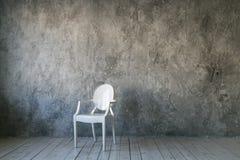 Vit plast- stol på betongväggbakgrund Vindrum floor trä Dagsljus Fritt avstånd för text royaltyfri fotografi
