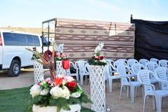 Vit plast-stolar, matta, bil och bukett av blommor för beduinbröllop Royaltyfri Foto