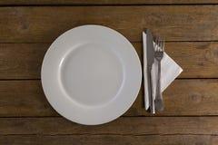 Vit platta med bestick och servett på tabellen Arkivbilder