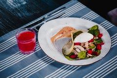Vit platta med det tjuvjagade ägget i sallad med kniven och gaffeln Nästa exponeringsglas med röd fruktsaft Blå bordduk på bakgru Arkivfoton