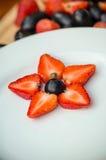 Vit platta med druvor och jordgubbar, stjärnaform arkivbilder