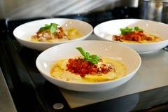 Vit platta med färgrik italiensk pasta Bolognese, krämig gul sås och gräsplanbasilika Royaltyfria Bilder