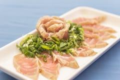 Vit platta med japansk mat på blå bakgrund royaltyfri fotografi