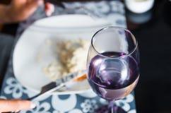 Vit platta med mat överst, glass framme som fokuseras innehålla klar flytande inom, flott matställeportioninställning royaltyfri bild