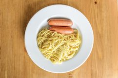 Vit platta med spagetti och tv? korvst?llningar p? en tr?tabell, bakgrunden med mat begrepp av den smakliga men sjukliga fooen royaltyfri foto