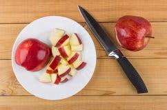 Vit platta med stycken av äpplet och kökkniven arkivbild