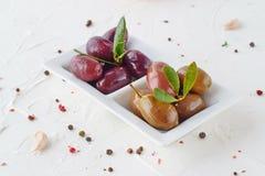 Vit platta med svarta och gröna oliv med olivgröna sidor på en vitabstrakt begreppbakgrund med citronen, körsbärsröd tomat arkivfoton