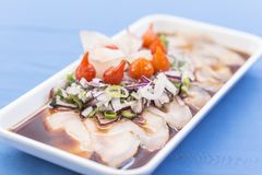 Vit platta med whitefishsashimien, den purpurfärgade löken, röd peppar, gräslökar och shoyu royaltyfria foton