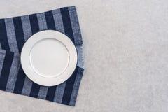 Vit platta och randig bordduk arkivfoto
