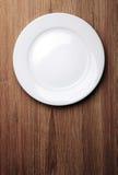 Vit platta på den wood tabellen Arkivfoto