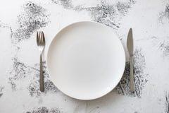 Vit platta på vit träbakgrund med redskap Royaltyfria Bilder