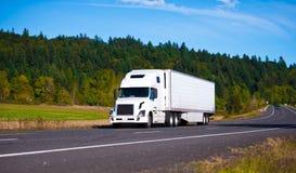Vit populär luxe halv lastbilsläp på den sceniska huvudvägen Royaltyfri Fotografi