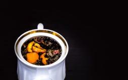 Vit porslinbryggare med en guld- gräns utan ett lock på en mörk bakgrund Bryggat te med apelsinen och blommor royaltyfri fotografi