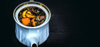 Vit porslinbryggare med en guld- gräns utan ett lock på en mörk bakgrund Bryggat te med apelsinen och blommor arkivfoton