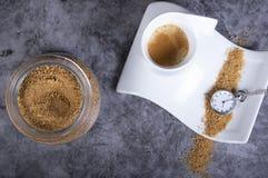Vit porslinkaffekopp med farin, sockerbunken och rovan som indikerar att det är dags att ha ett varmt kaffe med arkivbild