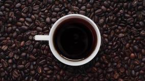 Vit porslinkopp kaffe bland kaffebönor Top beskådar arkivfilmer