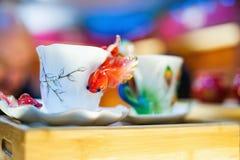 Vit porslinkopp med den guld- fisken arkivbild