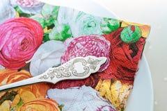 Vit porslinplatta med blommaservetten och den dekorerade kakagaffeln Royaltyfri Bild