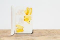Vit preventivpillerask med preventivpillerar på trätabellen på vit bakgrund Fotografering för Bildbyråer