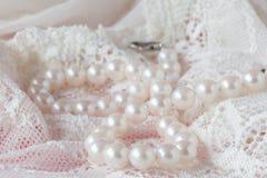 Vit pryder med pärlor halsbandet på toilettetabellen Selektivt fokusera arkivfoto