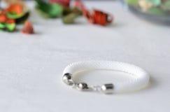 Vit prytt med pärlor virkat armband arkivfoto