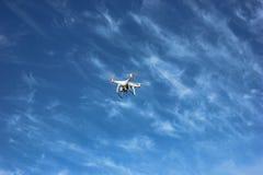 Vit quadrocopter flyger högt i luften Arkivfoto