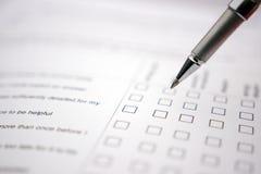 Vit questionare med pennan som väljer valet Arkivbild