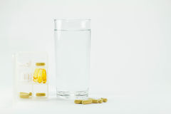 Vit räkningask med preventivpillerar, exponeringsglas av vatten och preventivpillerar på golv på Arkivfoto
