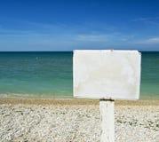 Vit rådgivningpanel på en strand med havet på bakgrunden för grafiskt begrepp arkivfoto