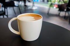 Vit rånar koppen som innehåller varmt cappuccinokaffe Royaltyfri Fotografi