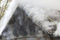 Vit rök kommer från det brinnande taket av huset arkivbilder