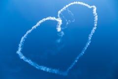 Vit rökhjärta i blå himmel Arkivfoto
