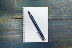 Röra sig i spiral anteckningsboken med skrivar på trägammala blått bordlägger Arkivfoto
